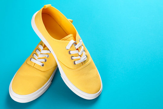 Pair of bright sneakers on colorful background. Space for text
