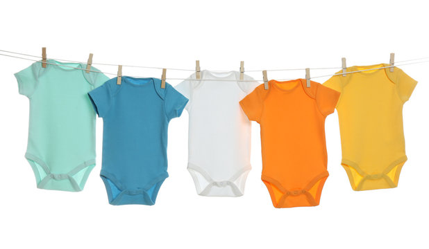 Colorful baby onesies hanging on clothes line against white background. Laundry day