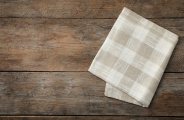 Folded kitchen towel on wooden table, top view. Space for text