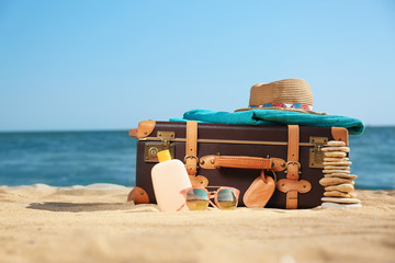 Suitcase and beach accessories on sand near sea. Space for text