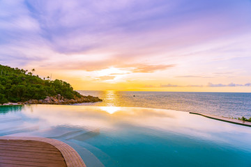 Beautiful outdoor infinity swimming pool in hotel resort with sea ocean view and white cloud blue sky
