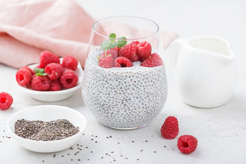 Healthy vanilla chia pudding in a glass with fresh raspberries .