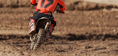 Racer child on motorcycle participates in motocross race, active extreme sport