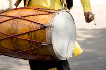 Dhol drummer playing this traditional indian instrument in the street