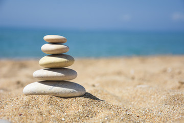 Balanced stone pyramid on sand on beach. Zen rock, concept of balance and harmony