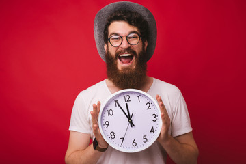 Photo of handsome excited bearded man, wearing a cowboy hat, holding clock  standing over red background