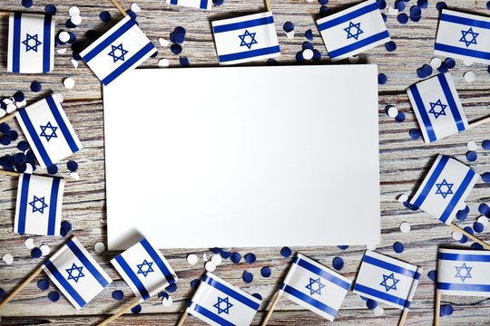 Israel independence day . April 29, 2020. white blue confetti paper with mini Israel flags and white sheet of paper on white wooden background , the concept of patriotism, strength and faith. mocup