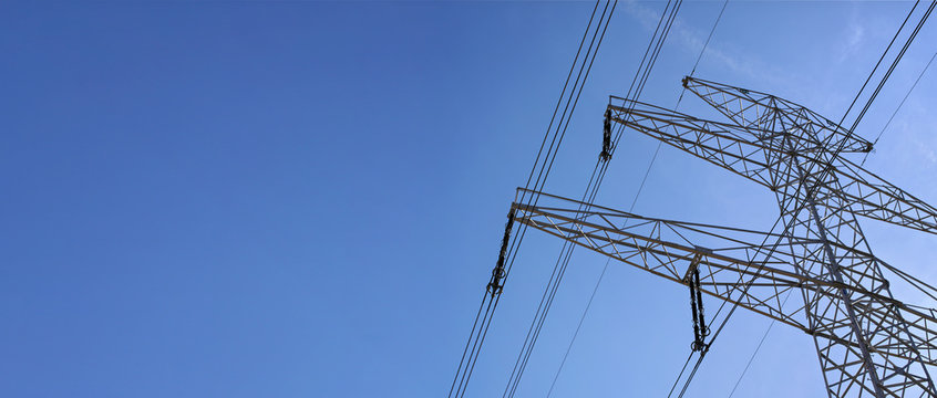Looking up steel power pylon construction with high voltage cables against blue sky. Wide banner for electric energy industry with space for text on left side