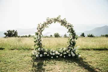Beautiful wedding arch of flowers or white roses in a field or meadow. Preparation for a wedding event. Fotomurales