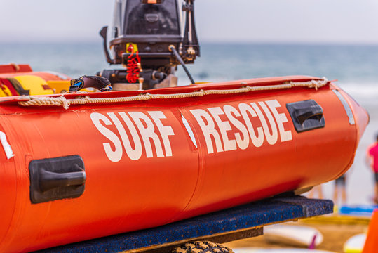 A red life saving surf rescue inflatable boat with a black outboard motor on the back