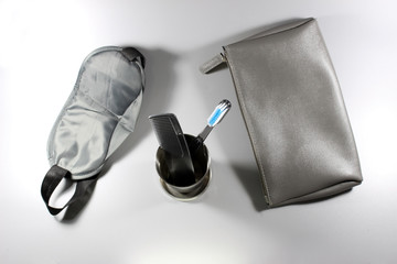 Items from a male toiletry kit, including bag, comb, toothbrush and sleeping mask