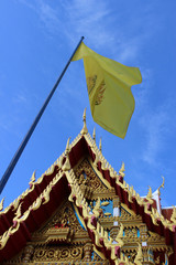 A traditional yellow flag flies in front of a traditional Buddhist Thai temple building and blue sky background.