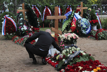 A man attends the funeral of Russian sailors killed in a fire on a submarine in Saint Petersburg