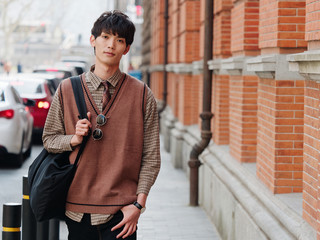 Portrait of a handsome Chinese young man with Korean style clothes walking and looking at camera with sad expression against Shanghai street background, male fashion, cool Asian young man lifestyle.