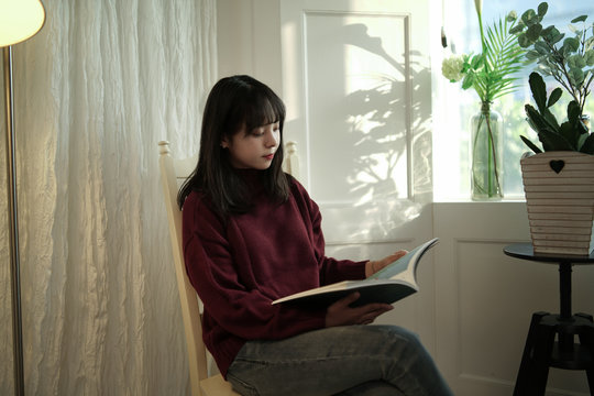 young woman reading book sitting beside window