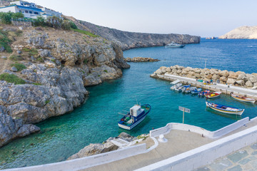 Little port with colorful fishing boats and turquoise sea waters in Potamos village in Antikythera island in Greece