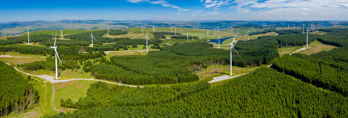 Fototapeta Aerial drone panorama of turbines at a large onshore windfarm in Wales, UK obraz