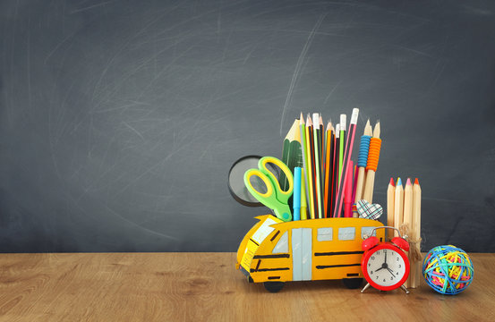 education and back to school concept. pencils stand as bus over wooden desk infront of classroom blackboard