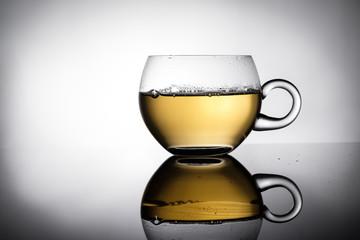 Tasse aus Glas mit Tee in Gegenlicht