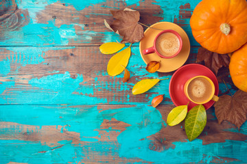 Autumn background with coffee cups, fall leaves and pumpkin on wooden table.