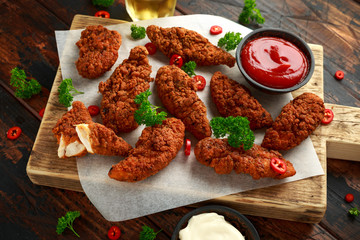 Breaded chicken strips with beer, ketchup and mayonnaise on wooden board