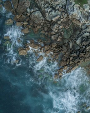 Aerial shot of a rocky beach with the splashing waters washing the stones