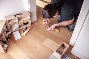 Obraz Handwerker bessert Fehlstellen im Parkett mit Reperaturset aus - fototapety do salonu