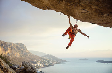 Young man climbing challenging route in cave