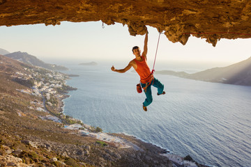 Rock climber hanging on cliff with one hand and showing thumb up