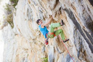 Young man climbing challenging route on cliff