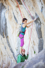 Female rock climber standing on shoulders of her partner in order to start climbing challenging route