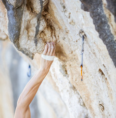 Climber's hand gripping handhold on cliff