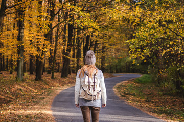 Hiking woman on her journey in autumn forest