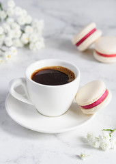 A cup of coffee and french macarons on a white marble background. Close-up. Selective focus