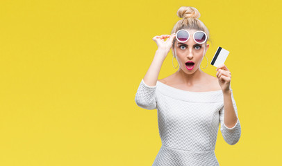Young beautiful blonde woman holding credit card over isolated background scared in shock with a surprise face, afraid and excited with fear expression