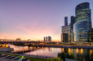 Wall Mural - Moskva River with skyscrapers and bridge at dusk, Moscow, Russia. Cityscape of Moscow in twilight. Modern buildings on background of sky in sunset light. Evening scenic view of Moscow-City embankment.