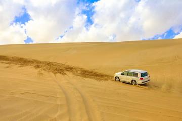 Aluminium Prints Landscapes Off-road adventure with SUV in Arabian Desert. 4x4 vehicle bashing through sand dunes at Khor Al Udeid, the inland sea near Qatar and Saudi Arabian, Persian Gulf, Middle East.