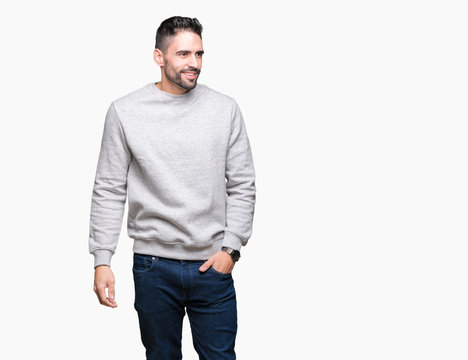 Young handsome man wearing sweatshirt over isolated background looking away to side with smile on face, natural expression. Laughing confident.