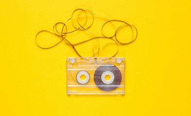 Music lover minimalism concept. Retro style 80s. Audio cassette with film on yellow paper background.