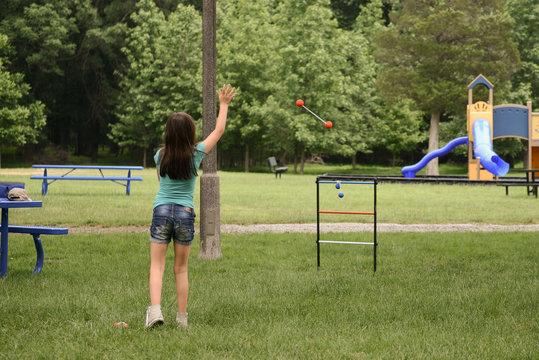 Girl plays ladder toss in public park