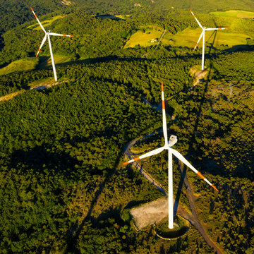 Wind turbines farm from above in the countryside