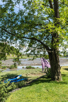 idyllic scene of Duck Creek in Wellfleet, Massachusetts with bright blue kayaks and laundry on a clothes line blowing in the breeze