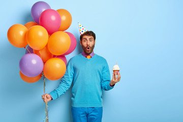 Surprised young man celebrates birthday, holds muffin with burning candle, bunch of colored air balloons, shocked with unexpected news, enjoys party. Blue colors. Time for fun and entertainment