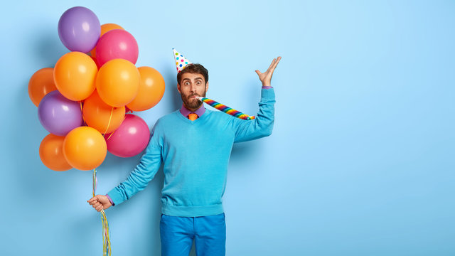 Attractive male model blows party horn, comes to congratulate best friend with anniversary, holds multicolored balloons, wears neat blue clothing, celebrates festive event. Man with holiday attributes