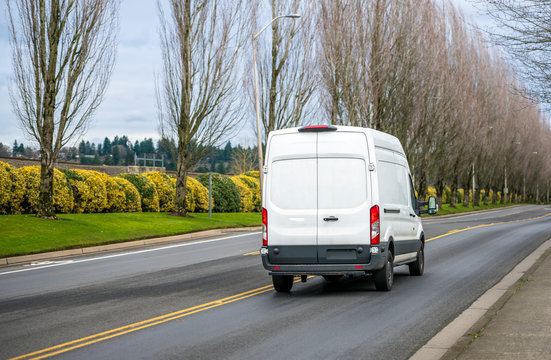 White compact commercial cargo mini van running on the road with trees alley