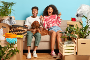 Overjoyed first time home buyers enjoy relocation, being tenant of new apartment, relaxes before unpacking boxes, sit on comfortable sofa in empty room with blue wallpapers, dog between them
