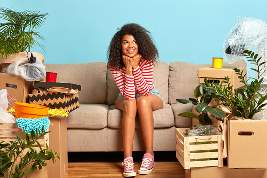 Delighted female apartment owner has dreamy expression, dressed in casual clothes, sits on sofa at cozy living room, carton boxes around, thinks about good future in own rental house, looks up