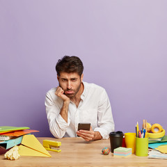 Dissatisfied offended male worker checks balance online, holds cellular, dressed in white shirt,...