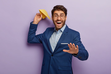 Handsome glad smiling banker throws paper plane makes wish, stretches hand, wears round spectacles, elegant formal suit, isolated on purple background. Business, achievement and success concept