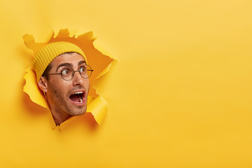Overwhelmed young guy keeps head through torn hole in yellow background, keeps jaw dropped, gazes aside on free space, notices something surprising, wears hat and big round glasses. Reaction